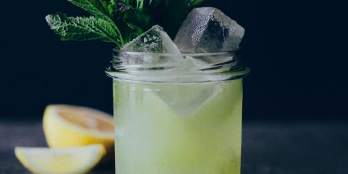 This is a front closeup of a glas filled with a green and yellow cocktail, decorated with ice cubes, lemon slices and lemon balm leaves