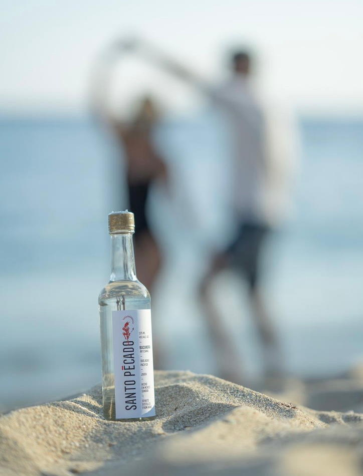 This picture shows a bottle of Santo Pecado Bacanora in the sand with people dancing Salsa on a sunny beach in the background